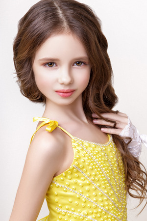 Little beautiful model girl with long wavy hair dressed in yellow dress posing in studio on a white background