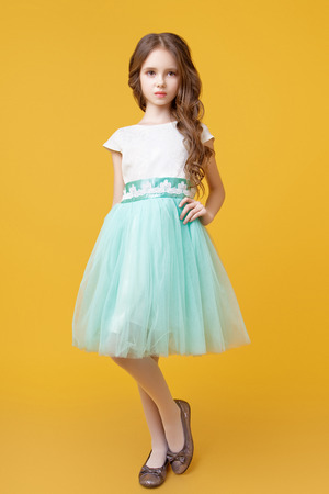 Little beautiful model girl with long wavy hair dressed in a white t-shirt and a sumptuous tulle skirt mint color poses in the studio on a yellow background
