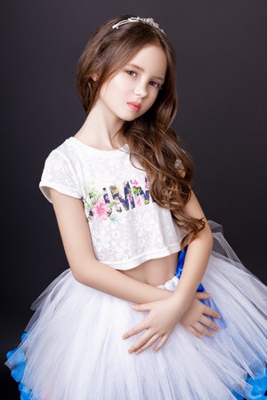 Little beautiful model girl with long wavy hair dressed in a white t-shirt and a sumptuous tuxedo skirt posing in the studio on a black background Stock Photo