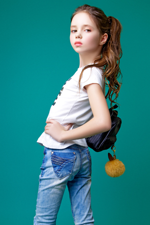 Little beautiful model girl with long wavy hair dressed in a white t-shirt and blue jeans holds a black backpack and poses in the studio on a green background Stock Photo