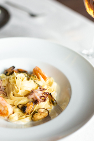 Seafood kraft paste: mussels, shrimps and octopus in a creamy sauce, served on a white plate on a table with a white tablecloth, instruments and a glass of wine in a restaurant Reklamní fotografie