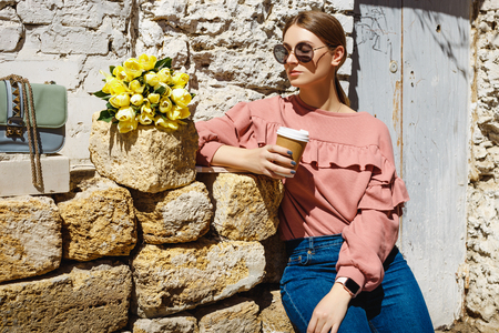 A girl stands near the urban wall with a cup of coffee, yellow tulips and a magazine in the bright sunshine on a warm spring day