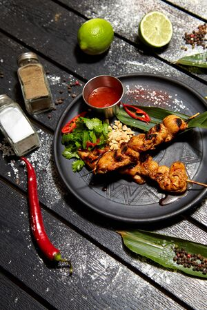 Asian dish on a black plate on a wooden table decorated with lime, pepper, salt, chili and flour. Appetizing chicken satay with tomato sauce. Restaurant serving