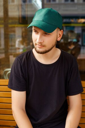 Attractive man wearing a green cap, black t-shirt and pants sits near a coffee shop on a summer day