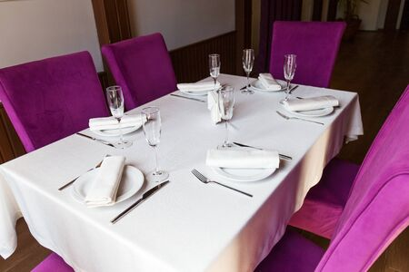 Table setting for the holiday, white tablecloth dishes and appliances on the table in the restaurant hall with purple chairs Archivio Fotografico