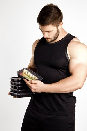 Attractive sporty man dressed in a black tank top and shorts, posing in the studio on a white background with boxes of food. Healthy nutrition, daily diet