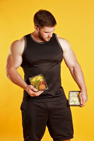 Attractive sporty man dressed in a black tank top and shorts, posing in studio on a yellow background with boxes of food. Healthy nutrition, daily diet Stock Photo - 128502940