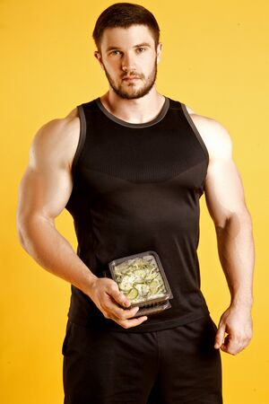 Attractive sporty man dressed in a black tank top and shorts, posing in studio on a yellow background with boxes of food. Healthy nutrition, daily diet Stock Photo