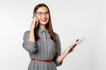 Beautiful girl with dark hair, dressed in a gray elegant dress and glasses in a business style in the studio on a white background. Talking on the phone smilingly and holding a notepad