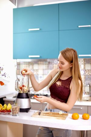 Attractive girl with blond hair makes a smoothie in a blender with orange, banana and strawberries in the turquoise kitchen. The concept of proper nutrition, diet