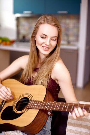 Aantrekkelijk meisje met blond haar speelt een akoestische gitaar zittend op een bank in een appartement. Muziek lessen concept Stockfoto