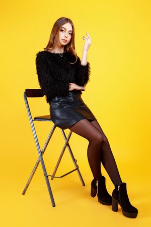 Beautiful young girl dressed in a black sweater and leather skirt posing in the studio on a yellow background. Fashion concept