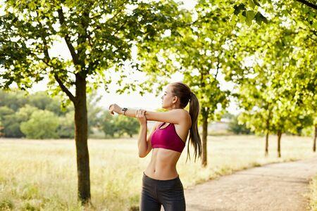 Schönes blondes gesundes Mädchen, das Sportkleidung trägt, die an einem Sommerabend im Park Übungen macht