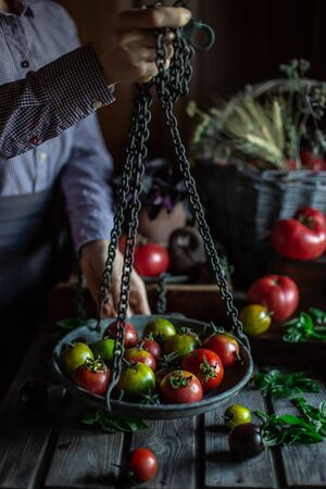 Hands holds a bowl of vintage scales on chains with heirloom tomatoes.