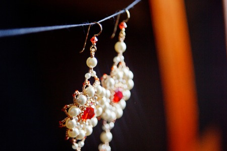 handmade jewelry made of beads in macro. earrings from white beads. earrings from stones. beautiful ornaments. earrings from red beads. ornaments on a black background