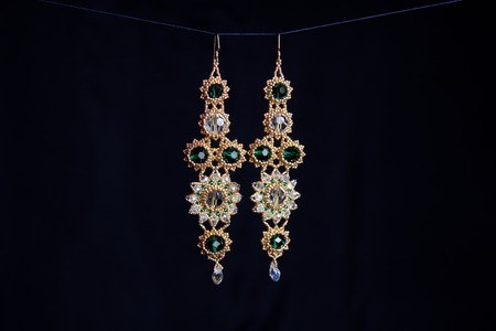 handmade jewelry made of beads in macro. earrings from white beads. earrings from stones. beautiful ornaments. earrings from golden beads. ornaments on a black background