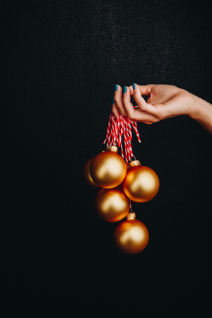 golden Christmas balls in hand isolated on black background. new year card Banque d'images