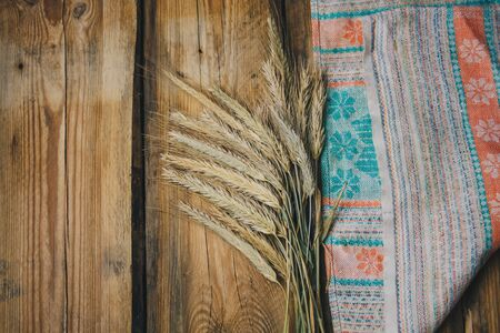 Spikelets on a towel in a rustic style on a white wooden table