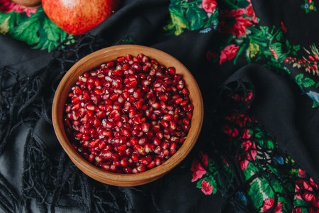 pomegranate grains in a ceramic bowl on a vintage background, pomegranate fruit, ceramic jug, ceramic plate, ethnic shawl, Romma shawl, still life