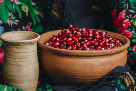 pomegranate grains in a ceramic bowl on a vintage fabric background, pomegranate fruit, ceramic jug, ceramic plate, ethnic shawl, Romma shawl, still life