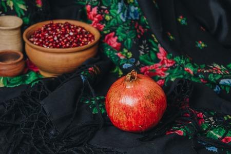 pomegranate grains in a ceramic bowl on a vintage background, pomegranate fruit, ceramic jug, ceramic plate, ethnic shawl, Romma shawl, still life