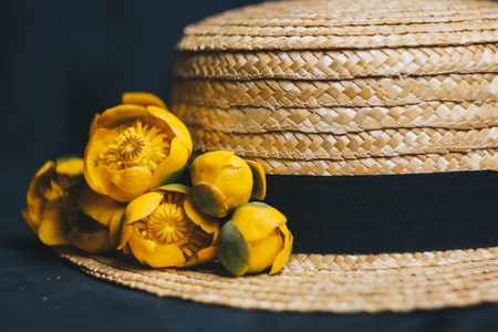 still life shell of a snail against the background of a summer straw hat with flowers of water lilies and beads of pearls. yellow colorful water lilies close-up. beach season. yellow flowers in a hat