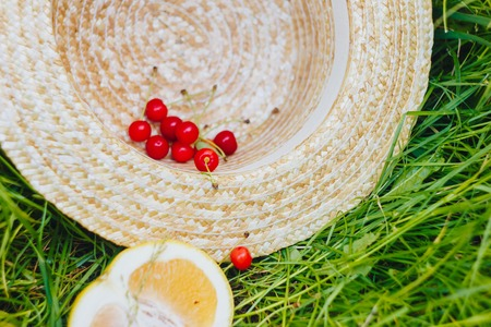 cherry and cuted citrus fruits with straw hat lying on the grass outdoors. Picnic on nature in the park close up healthy food, diet, personal care. sunny day