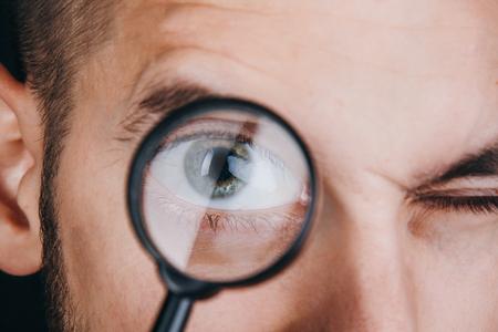un joven con barba mira a través de una lupa. Retrato de un chico con un gran ojo sobre un fondo negro. investigación, encuesta.