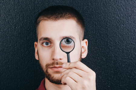 a young man with a beard looks through a magnifying glass. Portrait of a guy with a big eye on a black background. investigation, survey.
