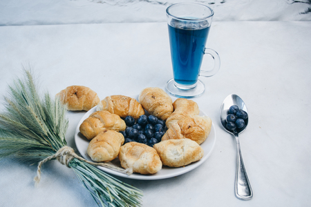 healthy light breakfast. blue tea from orchids, blueberries on a spoon, croissant on a plate with spikelets of wheat. top view proper nutrition for a slim figure. raw food vegetarianism. diet.