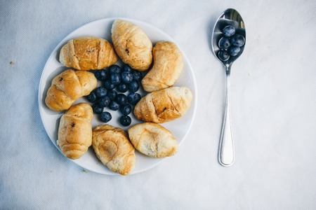 healthy light breakfast. blueberries on a spoon, croissant on a plate with spikelets of wheat. close up. proper nutrition for a slim figure. raw food vegetarianism. diet.