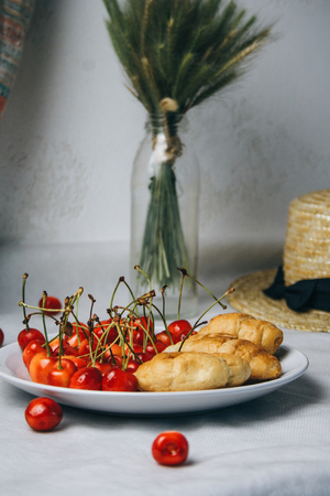 healthy light breakfast. sweet cherry with croissants on a plate. bouquet in a vase with spikelets of wheat. tea in a cup. Straw hat. proper nutrition for a slim figure. raw foods vegetarianism. diet.