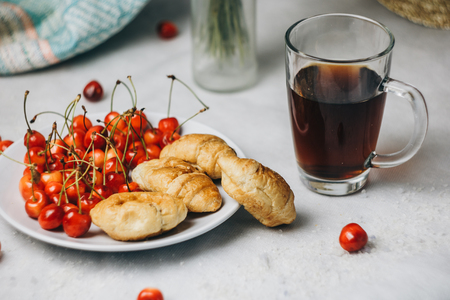 healthy light breakfast. sweet cherry with croissants on a plate. bouquet in a vase with spikelets of wheat. tea in a cup. proper nutrition for a slim figure. raw foods vegetarianism. diet.