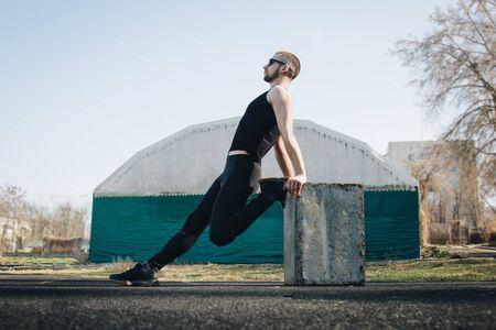Een slanke jonge man in zwarte kleding en zonnebril oefent buitenshuis. fitness atleet op het sportveld. trainen met projectielen. opwarmen benen strekken. lichaamsvoorbereiding voor de zomer.