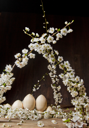 wooden easter eggs among flowering cherry branches on a rustic table. symbolic composition of the spring holiday for a gift card. copy space. close up. petals of white flowers. the rebirth of nature.