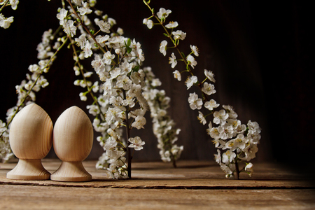 A couple of wooden Easter eggs among flowering cherry branches on a rustic table. symbolic composition of the spring holiday for a gift card. copy space. close up. white petals. the rebirth of nature.