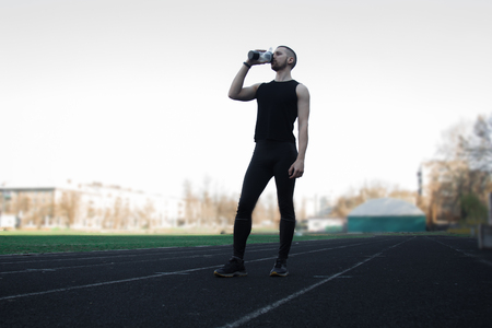 muscular slender man in training at the stadium drinks water from a sports shaker. recreation sports. athletic exercising.