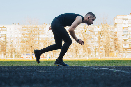 one caucasian male is doing a sprint start. running on the stadium on a rubber track. Track and field runner in sport uniform. energetic physical activities. outdoor exercise, healthy lifestyle.