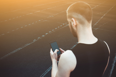 A young man in black clothes is looking at the phone. fitness athlete on the sports field. training with gadgets. warm up body preparation for the summer. run tracking.