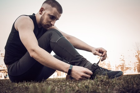 A young man in black clothes is tying the laces on the sneakers close up. fitness athlete sitting on the sports field on the grass. warm up body preparation for the training.