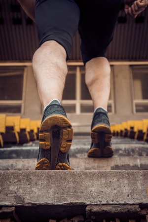 Caucasian man trains in running on the stairs. Track and field runner in sport uniform training outdoor. athlete, top view. step exercises. vertical. pumped up shanks close up.