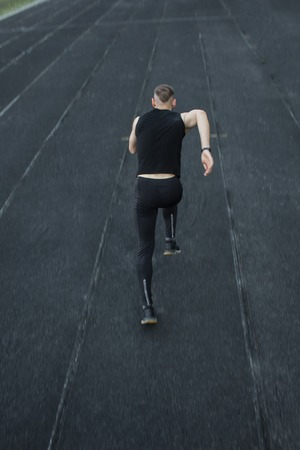caucasian man doing a sprint start. running on the stadium on a track. Track and field runner in sport uniform. energetic physical activities. outdoor exercise, healthy lifestyle. vertical top view.