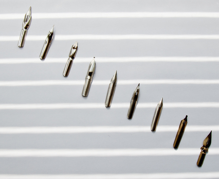 metal tips for the ink pen on a white background in solar rays. stationery on white desk close up top view. spelling lessons and caligraphy exercises. Template, layout, background. macro.