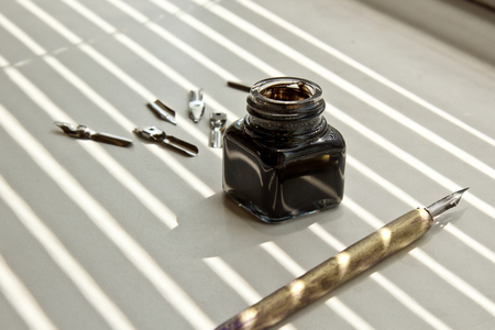 Inkpot with metal tips for the ink pen on a white background in solar rays. stationery on white desk close up top view. spelling lessons and caligraphy exercises. Template, layout, background.