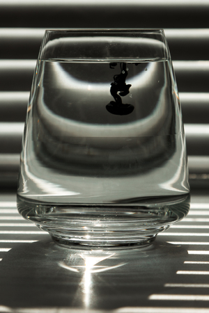 a cloud of ink in a transparent glass cup with clear water against the backdrop of a striped screen with rays of light. Template, layout, background, texture. macro diffusion black and white.