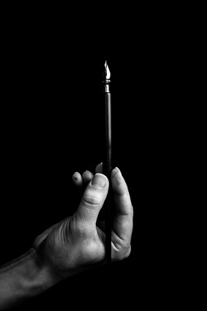 female hand elegantly holding an ink pen with a metal tip close-up on a black background. classic fountain pen isolated macro black and white. copy space. vertical.