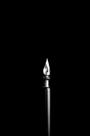 an ink pen with a metal tip close-up on a black background. classic fountain pen isolated macro black and white. copy space. vertical.