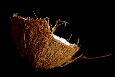 ripe coconut is broken into two halves isolated on a black background close-up. the insides of the tropical palm fetus.