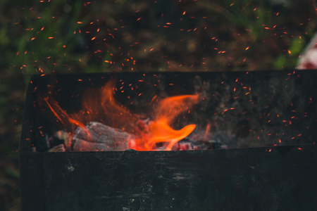 charcoal smolder in the iron grill. cooking picnic outdoors. sparks over the embers top view close up. Stock Photo