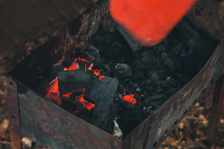 charcoal smolder in the iron grill. cooking picnic outdoors. sparks over the embers top view close up.
